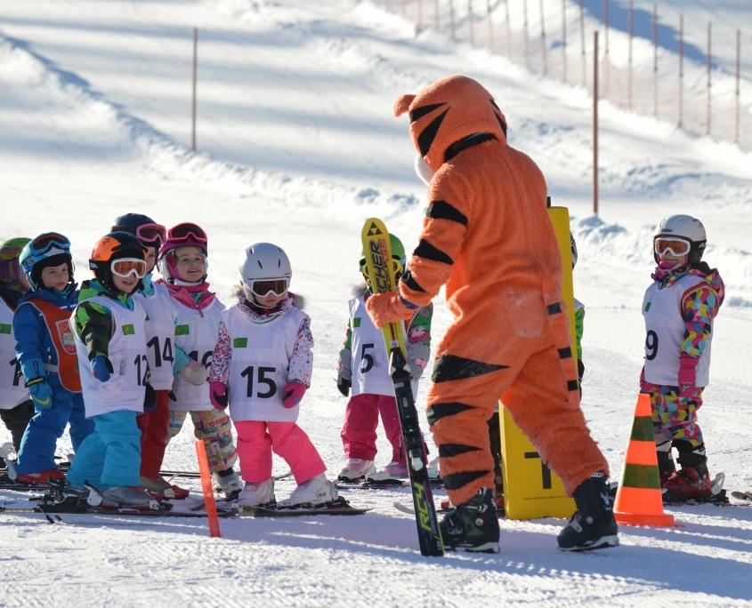 Kinder-Schikurs mit dem Tiger-Maskottchen der Schischule greenorange
